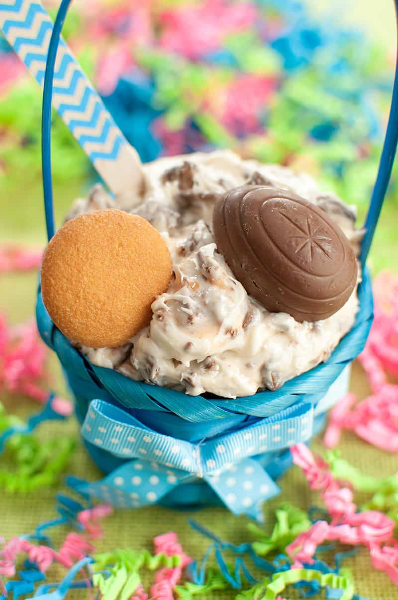 Easter basket with a bowl of Cadbury Creme Egg Dip topped with a vanilla wafer