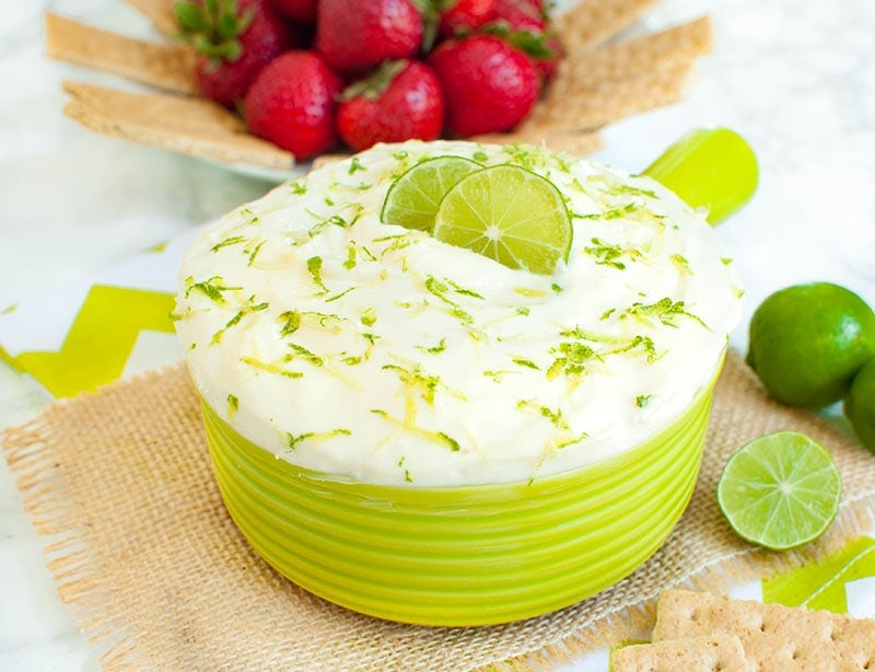 key lime pie dip in a green bowl with a plate of strawberries and graham crackers