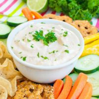 chipotle mayonnaise dip in a white bowl topped with parsley