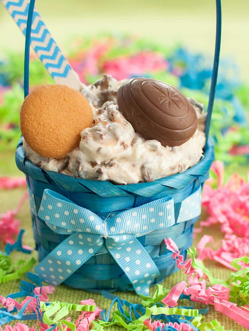 Small blue Easter basket filled with Cadbury Creme Egg Dip and topped with a vanilla wafer