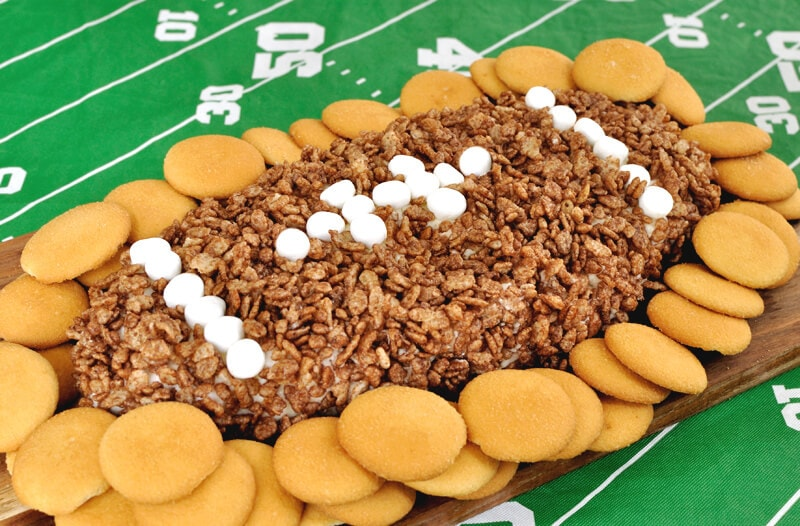 Fun appetizer or dessert recipe for game day. This Cocoa Krispie Treat Football Cheese Ball combines the flavor of marshmallow with cocoa krispies in a dip.