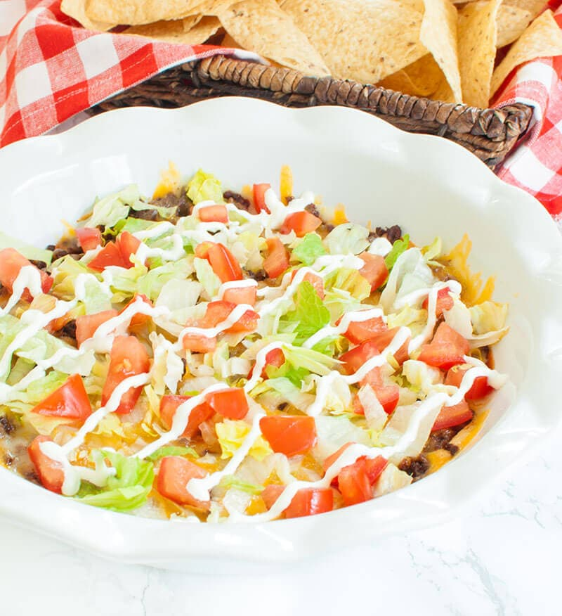 Taco dip with meat and cream cheese in a white pie dish