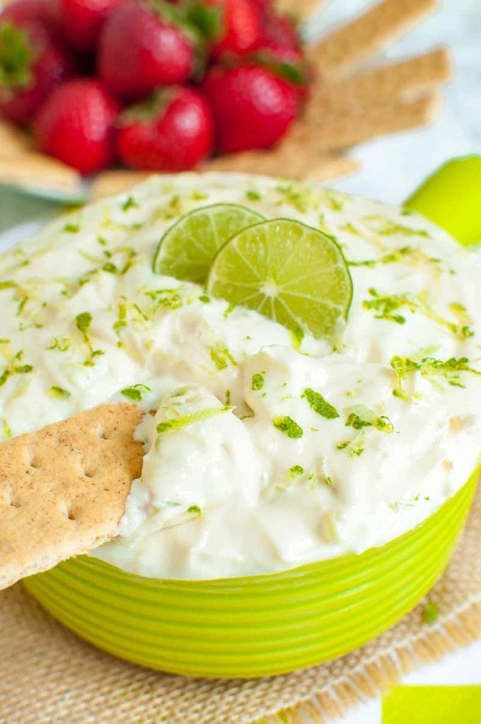 green bowl of key lime pie dip with a graham cracker dipped in