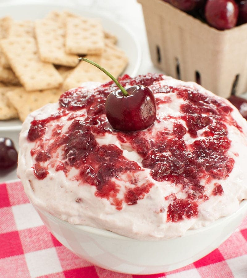 Cherry Cheesecake Dip in a bowl with a cherry on top
