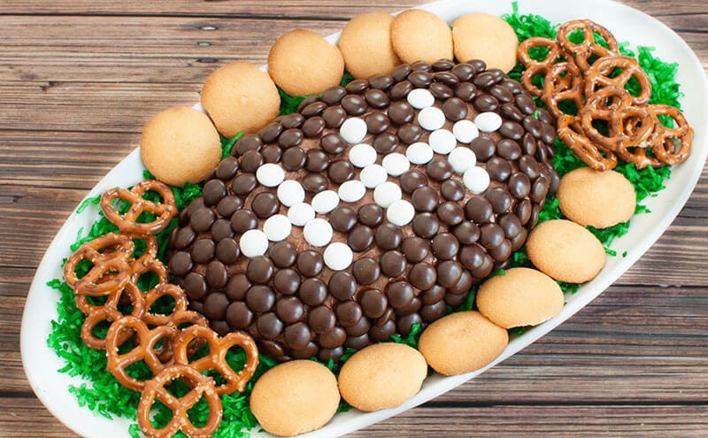 Chocolate Dessert Cheese Ball shaped like a football on platter with pretzels and vanilla wafers