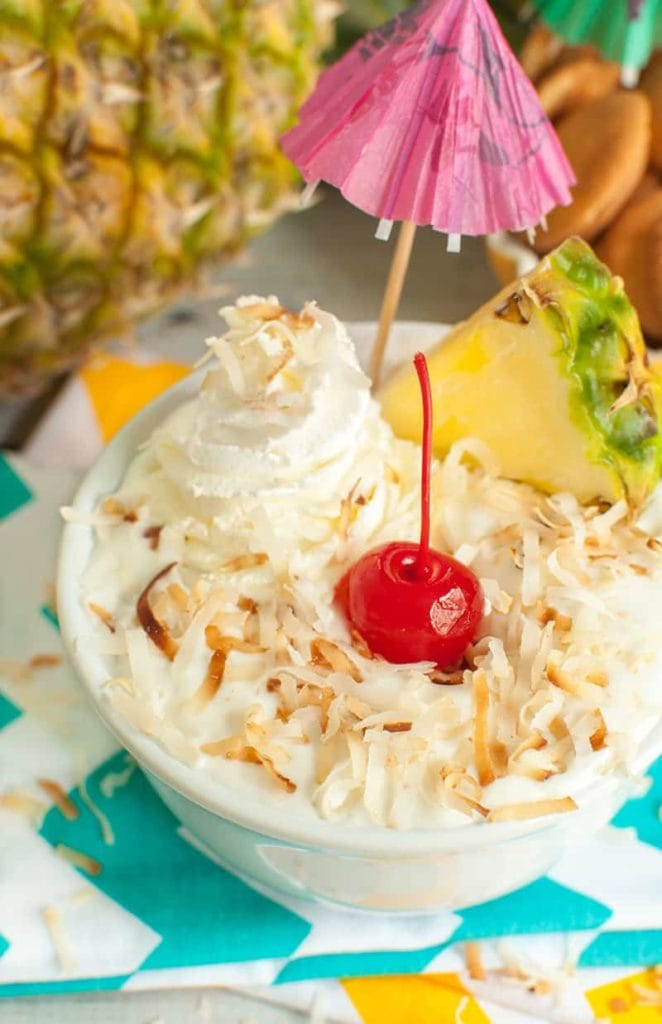 Toasted coconut, pineapple and a cherry on top of a bowl of pineapple dip aka pina colada dip