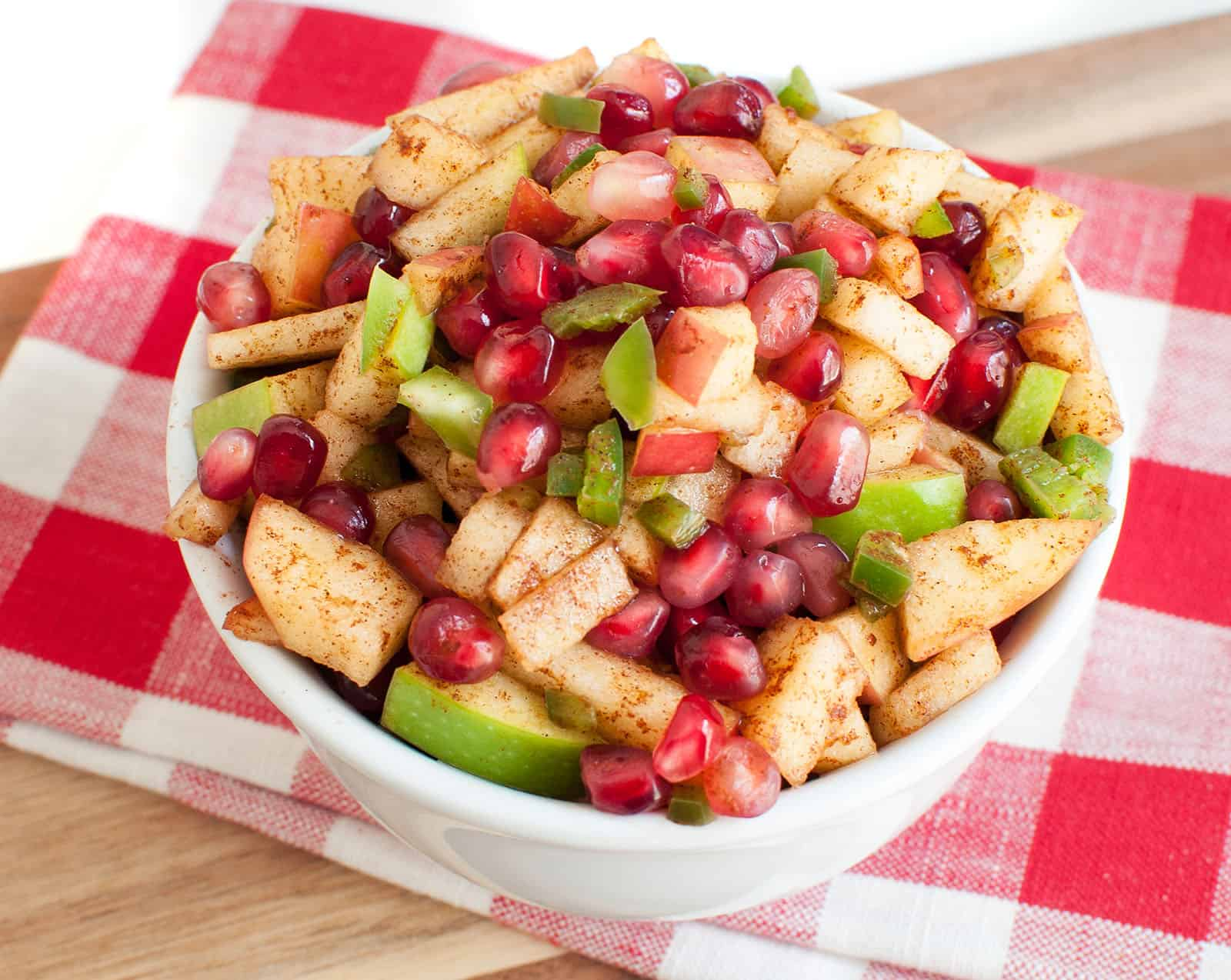 A bowl of apple salsa on a red and white checkered napkin