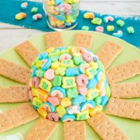 Lucky Charms Cheesecake Cheese Ball on green platter with graham crackers