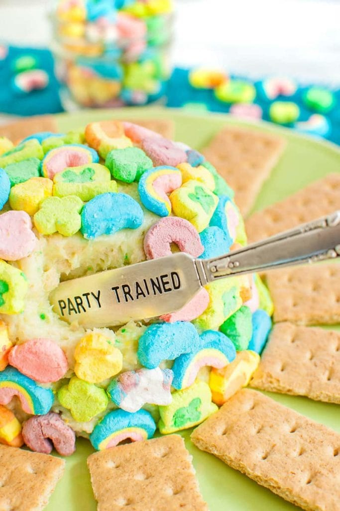bite cut out of a lucky charms cheesecake cheese ball with spreader that reads party trained