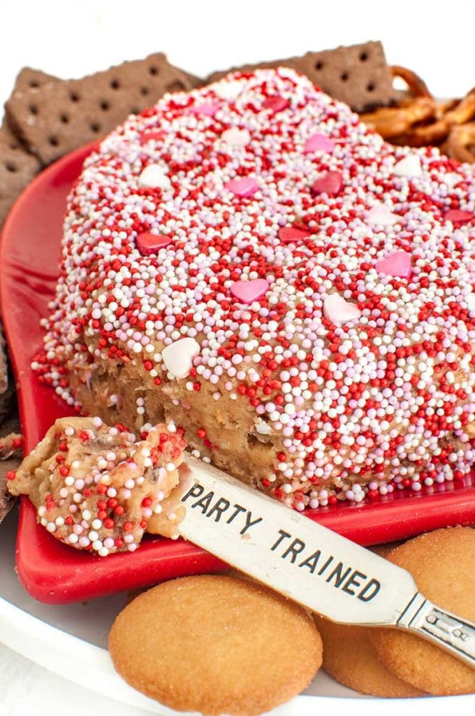 heart shaped peanut butter cheese ball with end scooped on a spreader that says I'm party trained