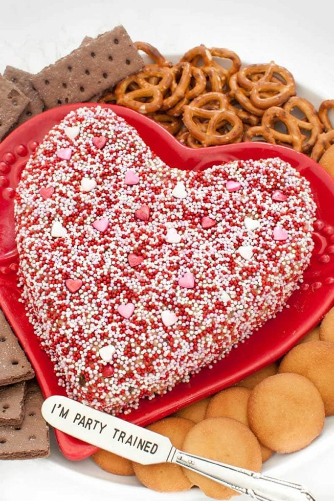 heart shaped peanut butter cheese ball on a red heart platter surrounded by cookies and pretzels