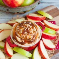 red bowl of caramel dip surrounded by apple slices