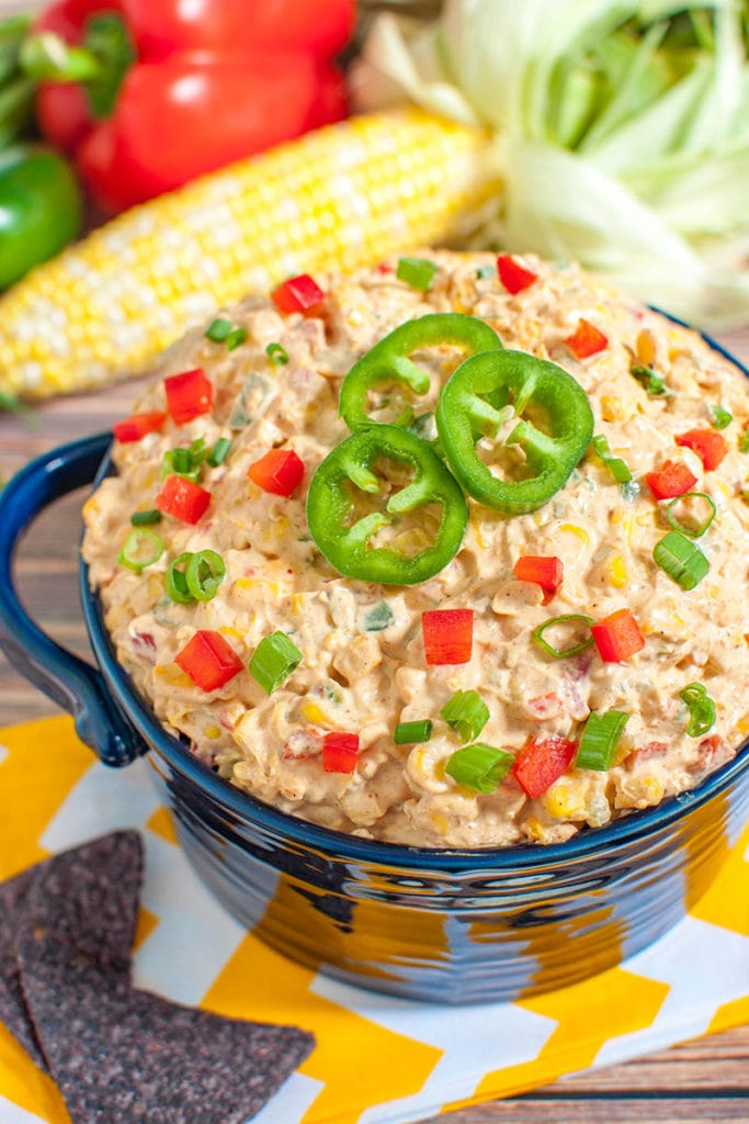 blue bowl of mexican corn dip topped with sliced jalapenos