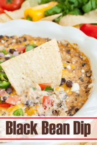 tortilla chip dipped into a dish of black bean dip