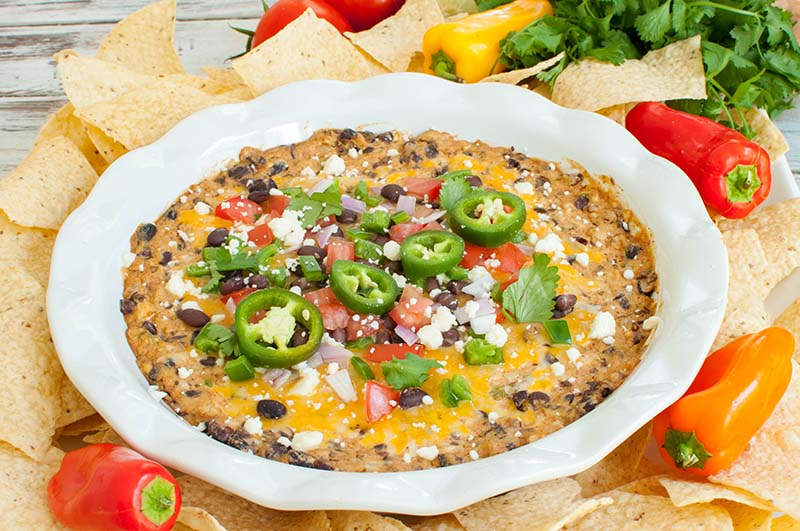 white round dish of black bean dip topped with jalapenos
