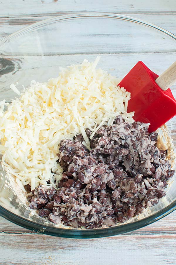 a bowl with black bean dip ingredients being mixed together
