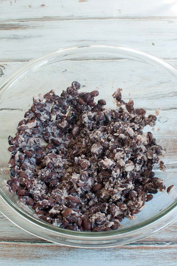 mashed black beans in a bowl for black bean dip
